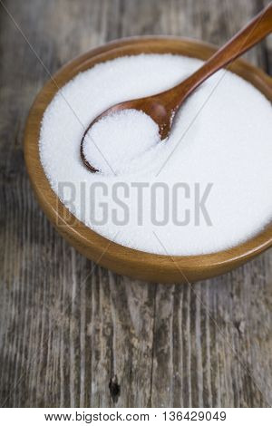 Sugar and spoon in a wooden bowl on the table