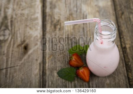 Strawberry smoothie on a wooden table ,