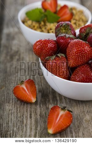 Ripe strawberries and granola on a wooden table