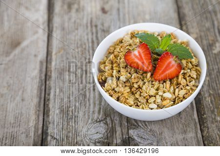 Granola With Strawberries On A Wooden Table