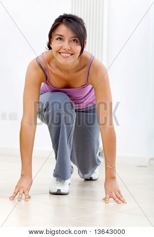 Fitness woman in a racing position smiling