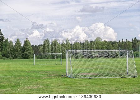 Soccer Goals on Soccer Pitch with a cloudy sky and trees.