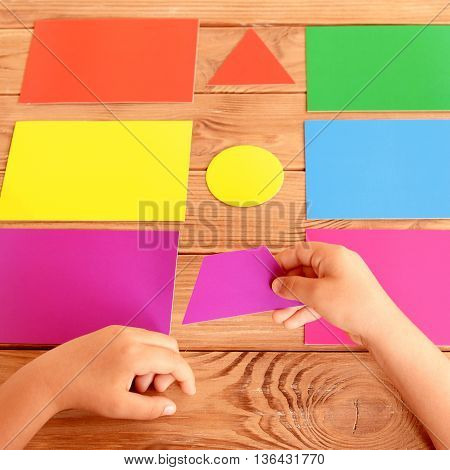 Child puts the cardboard figure on the corresponding colored card. Training set of cards for children on a wooden table. How to teach kid colors. Baby development