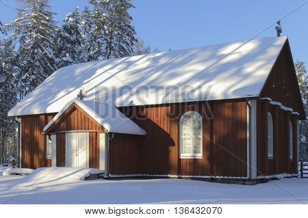 Wooden church in wintry countryside in Finland.