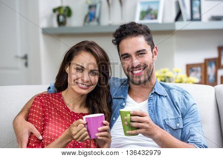 Portrait of smiling couple having coffee at home