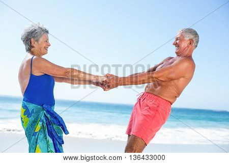 Cute mature couple holding hands on the beach on a sunny day