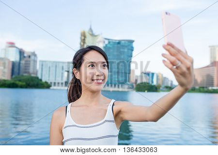 Woman taking selfie by mobile phone in Macao city
