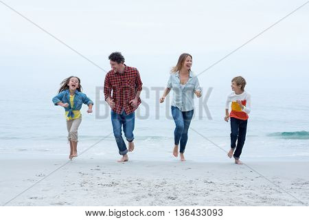 Full length of cheerful family running at sea shore against sky