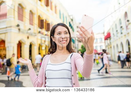 Woman use of mobile phone to take photo in Macao