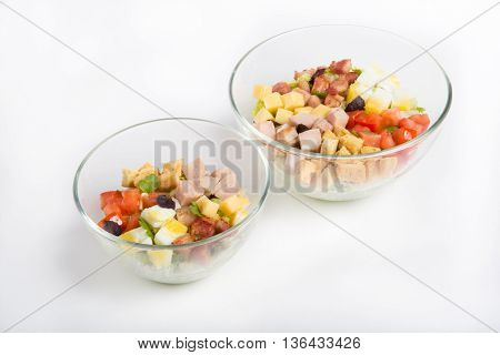 Salad with vegetables and bacon in a glass bowl