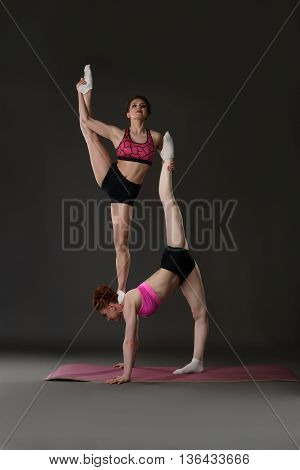Studio photo of female acrobats training in pair, on gray background