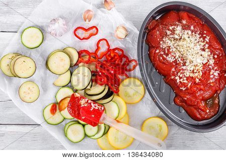 Raw ingredients zucchini bell pepper onion eggplant tomato sauce and garkic in baking dish dish for traditional French casserole - ratatouille