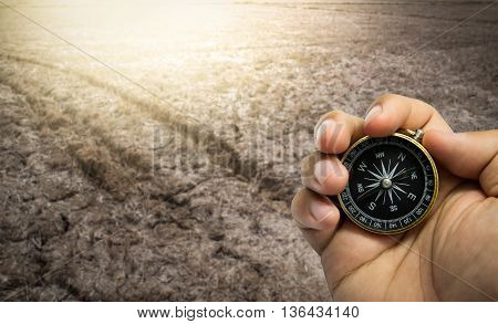 Compass in hand on a the route dry cracked ground.