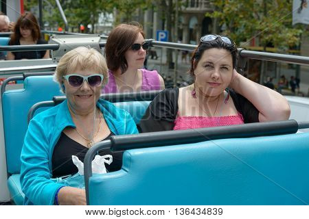 BARCELONA, CATALONIA, SPAIN - JUNE 16: Tourist women are going trough Barcelona streets by touristic bus sitting on blue seats of upper level of it on June 16, 2014 in Barcelona, Catalonia, Spain.