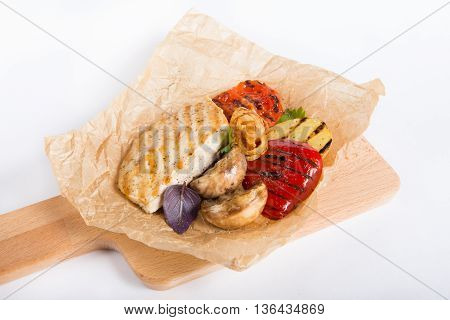 Chicken breast on roast with grilled vegetablesserved on wooden board