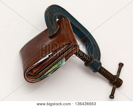 an image with a wallet and a vise that tightens wallet.
