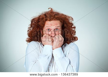 The young frightened man with long red hair looking at camera,