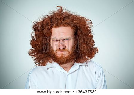 The young frowning with long red hair looking at camera