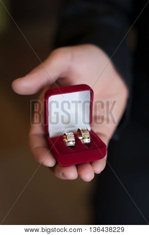 Groom holding wedding rings in the box close up