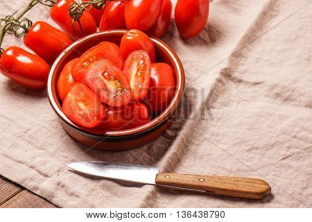 Ripe Organic red plum tomatoes. There is some whole tomatoes and other cut in a bowl