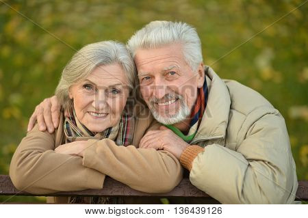 Portrait of a happy senior couple in autumn park