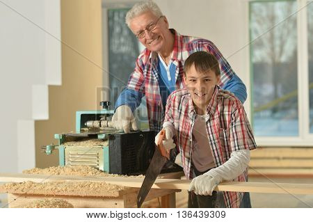 Senior  man and his grandson repairing in the room