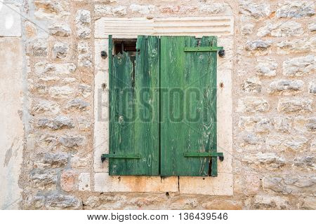 Closing green old wooden door on a brick wall
