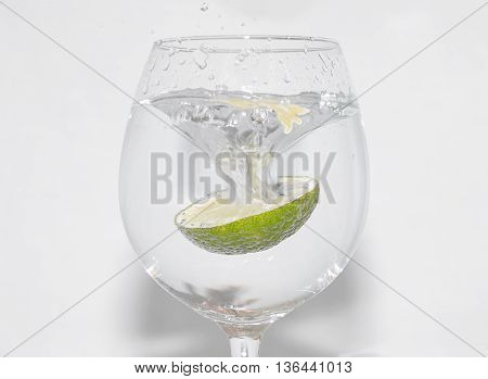 Slice of lime being dropped into a glass on white background
