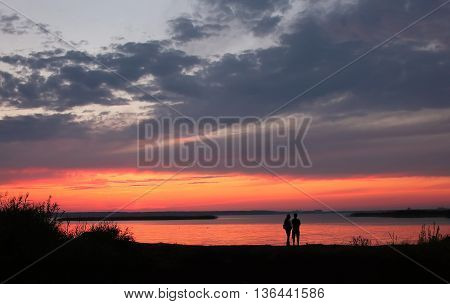 Couple at Beach on Sunset sky Background