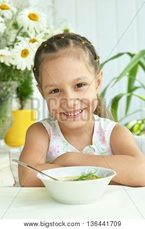 Portrait of  Beautiful little girl with soup