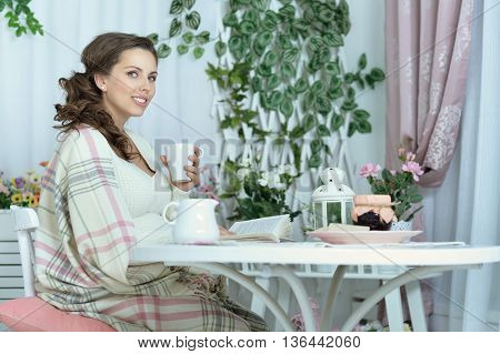 fashion photo of beautiful pregnant woman with long dark hair posing in studio interior with drink