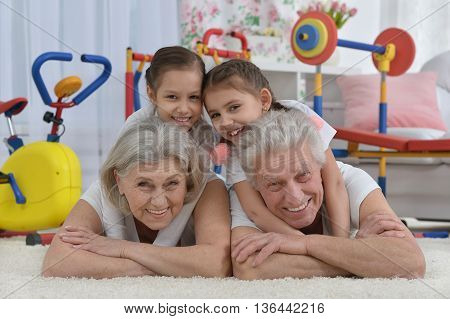 grandparents  and  little granddaughters doing exercise home