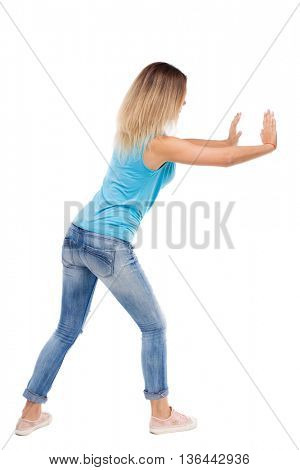 back view of woman pushes wall.  Isolated over white background. Rear view people collection. backside view of person. blonde in a blue shirt and jeans pushes something on my own.