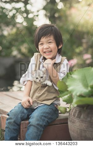 Cute Asian boy holding american short hair kitten with sunshine in the parkvintage filter