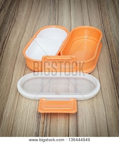 Orange folding plastic box for food storage on the wooden background. Open box. Kitchen equipment. Set of boxes.