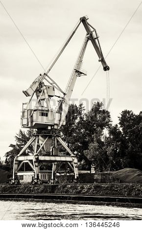 Crane in cargo port translating coal. Industrial scene. Black and white photo. Big port-crane. Vertical composition.