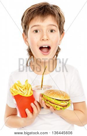 Happy nine year old boy holds french fries, burger and soda and smiling. Fast food. Concept of healthy and unhealthy food. Isolated over white.
