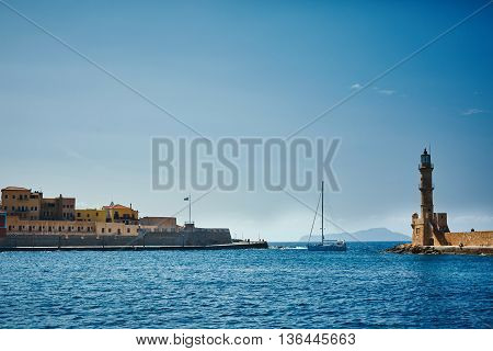 bay of Chania with lighthouse at sunny summer day, Crete, Greece. Yacht comes to the bay