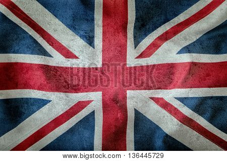 Closeup of Union Jack flag. UK Flag. British Union Jack flag blowing in the wind. Concrete background.