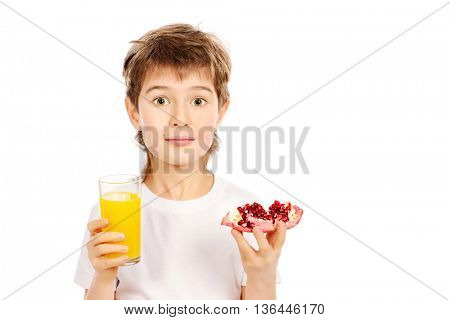 Happy boy holds juice and fresh pomegranate. Isolated over white.