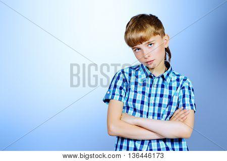 Close-up portrait of a serious boy at studio. Copy space.