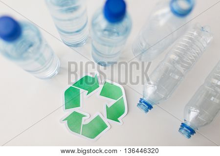 recycling, reuse, garbage disposal, environment and ecology concept - close up of empty plastic water bottles with green recycle symbol on table