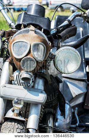 Detail of veteran motorbike with symbolic gas mask. Meeting bikers. Front view. Handlebars and headlight. Exhibitionism theme.