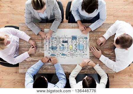business, people, technology and planning concept - close up of creative team with scheme sitting at table in office