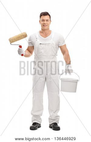 Full length portrait of a young male decorator holding a paint roller and a color bucket isolated on white background