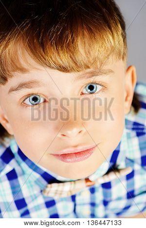 Close-up portrait of a smiling boy at studio.