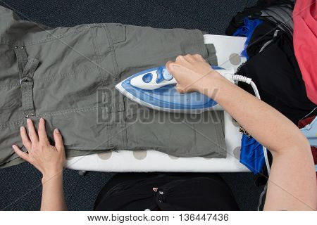 Woman Ironing Clothes On Ironing Board, Closeup Flat Lay