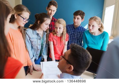 education, school, learning, teaching and people concept - group of students and teacher checking tests at school