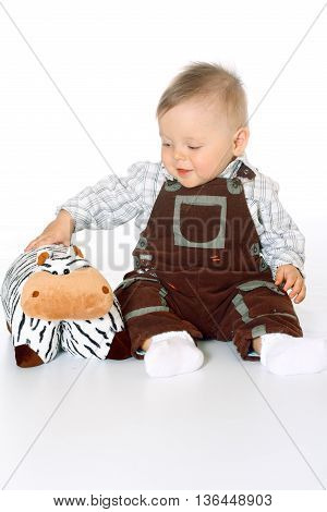 cute baby boy in brown jumpsuite sitting in the full-lenght and playing with toy cow of pillows, white background, isolated