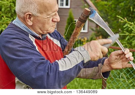 Hoary man sharpening scythe in front of his summer house